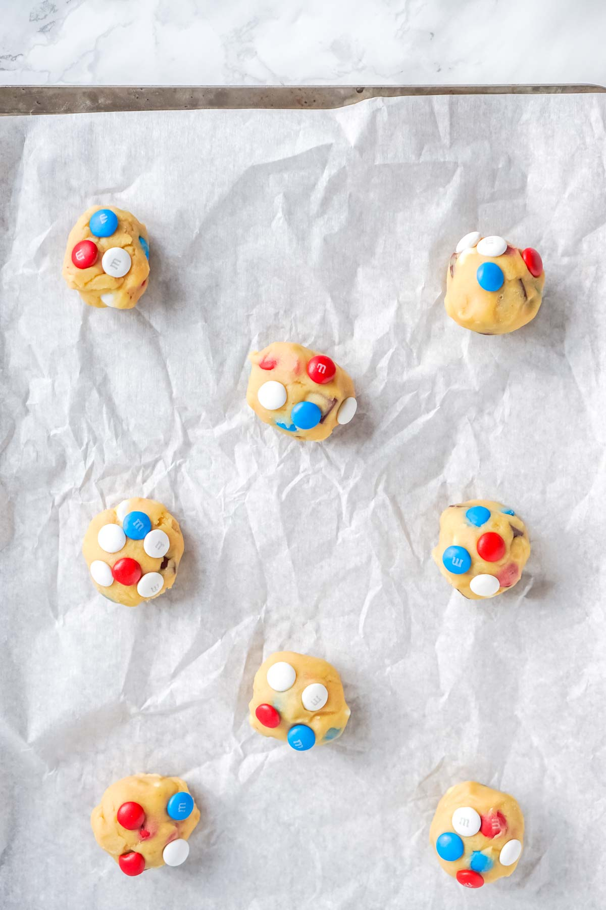 unbaked chocolate chip M&M cookies on a baking sheet