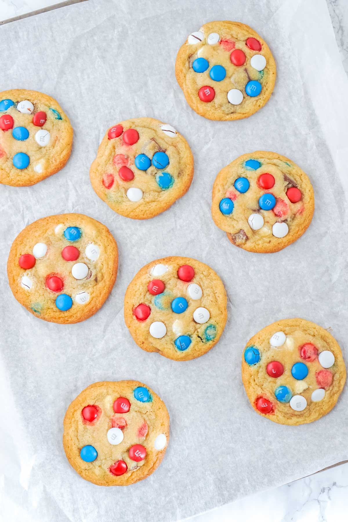 chocolate chip M&M cookies cooling on a piece of parchment paper