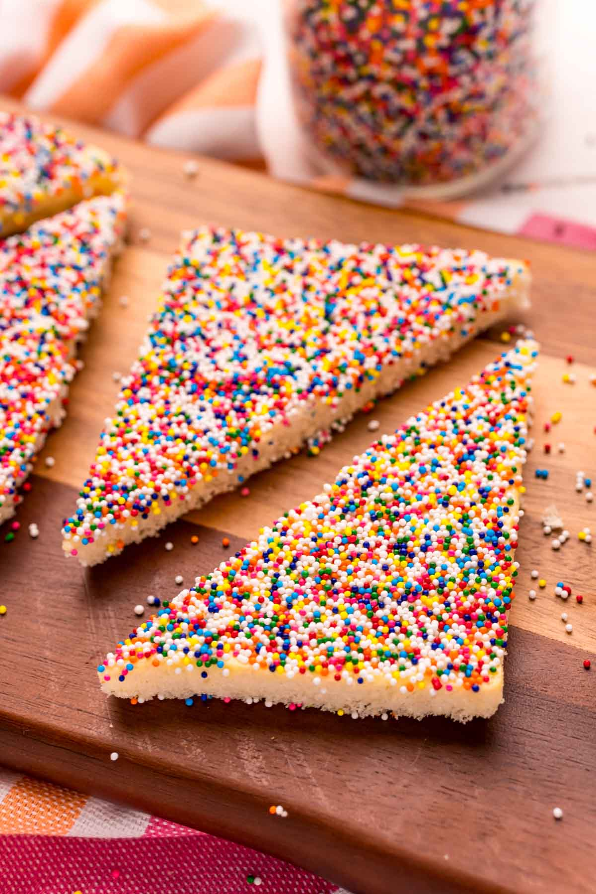 two pieces of fairy bread on a cutting board