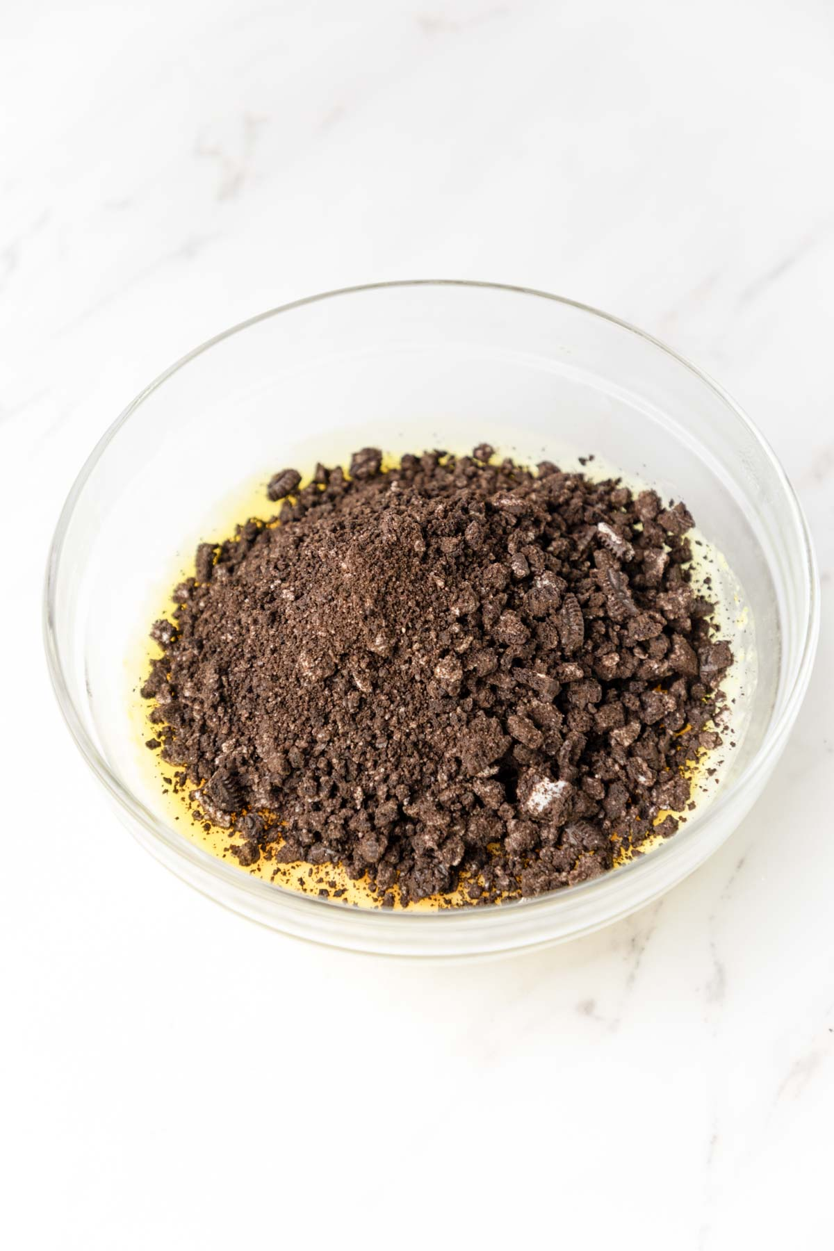 Oreo crumbs on top of vanilla pudding in a bowl