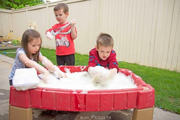 kids playing at a water table filled with foam