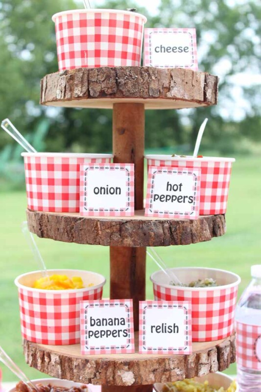 hot dog toppings in cups on a wood stand