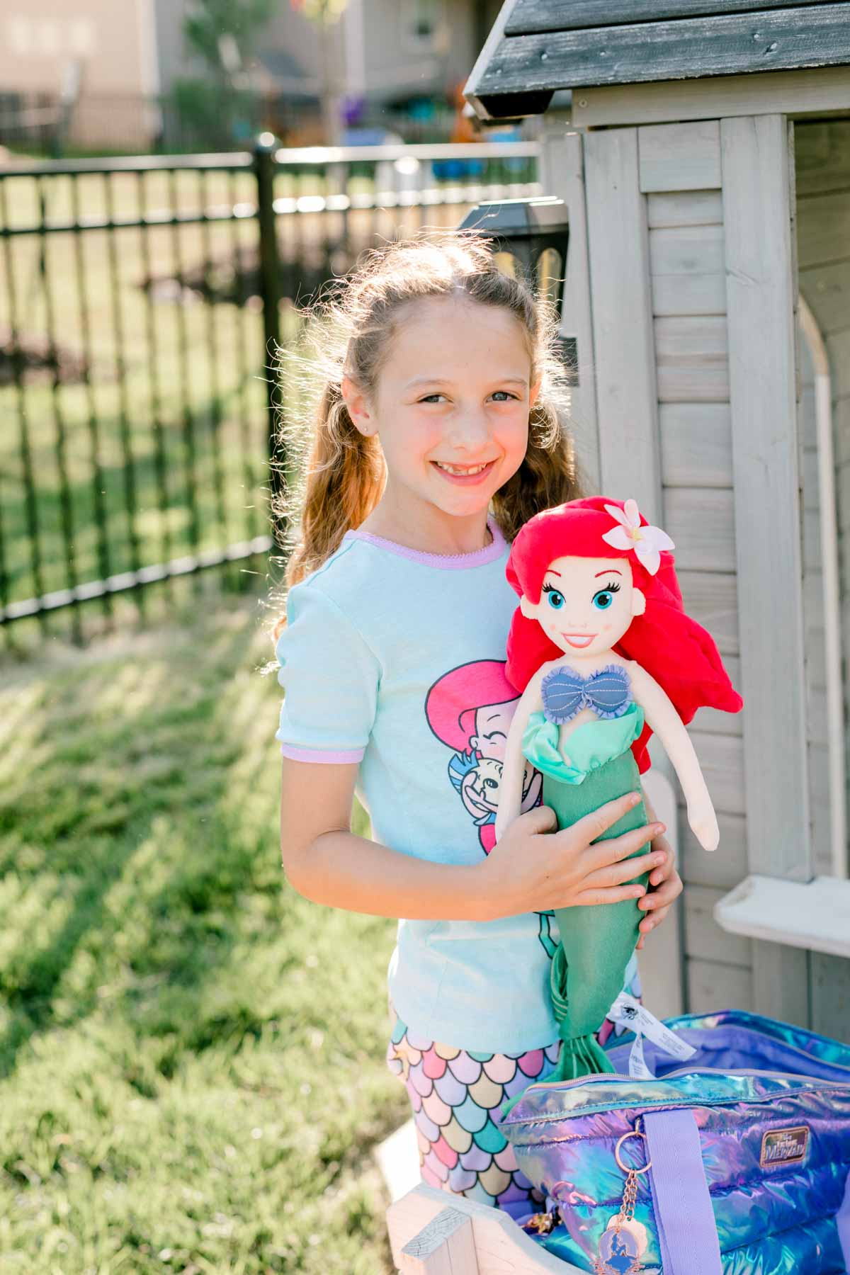 girl holding an Ariel plush