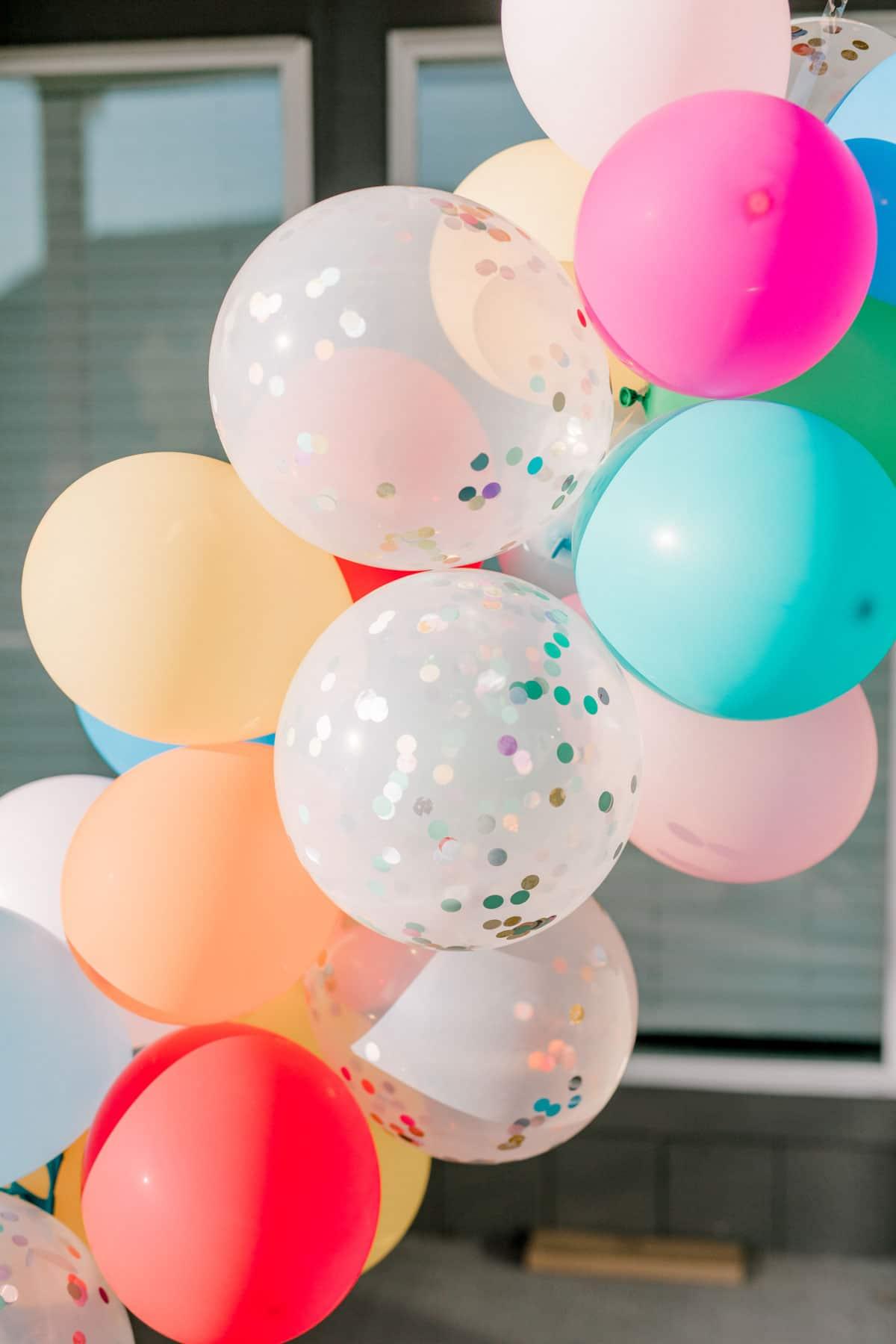 a balloon garland with confetti balloons