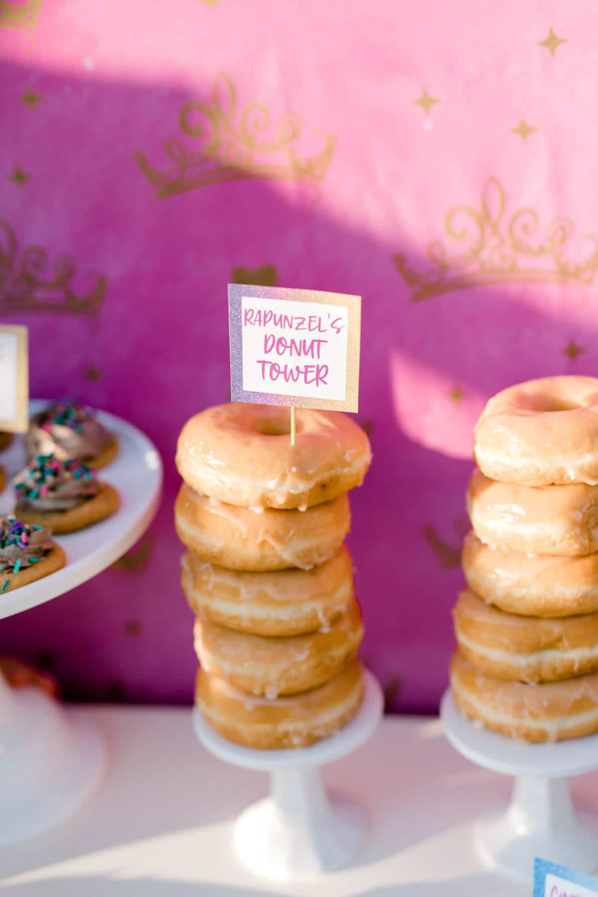 tower of donuts with a pink background
