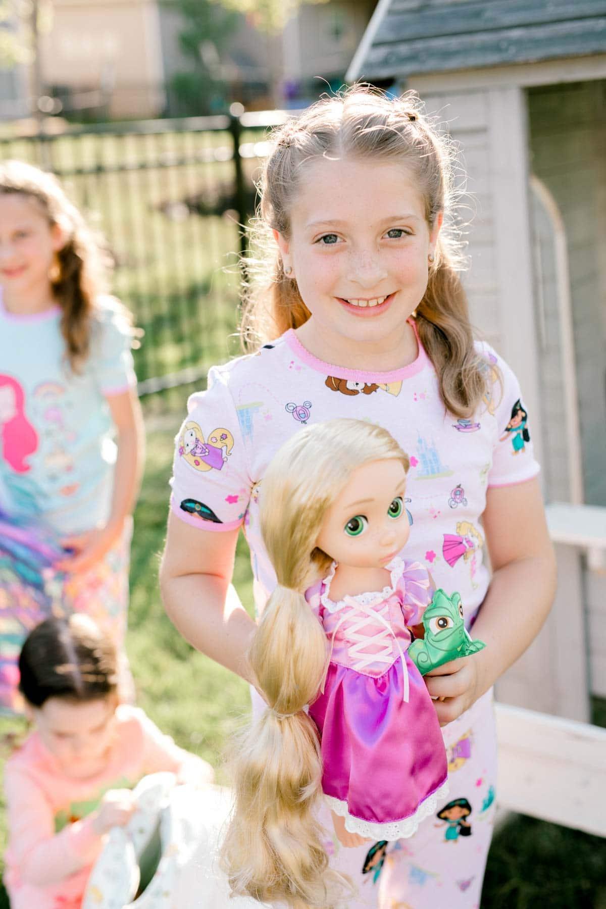 girl holding a Rapunzel doll