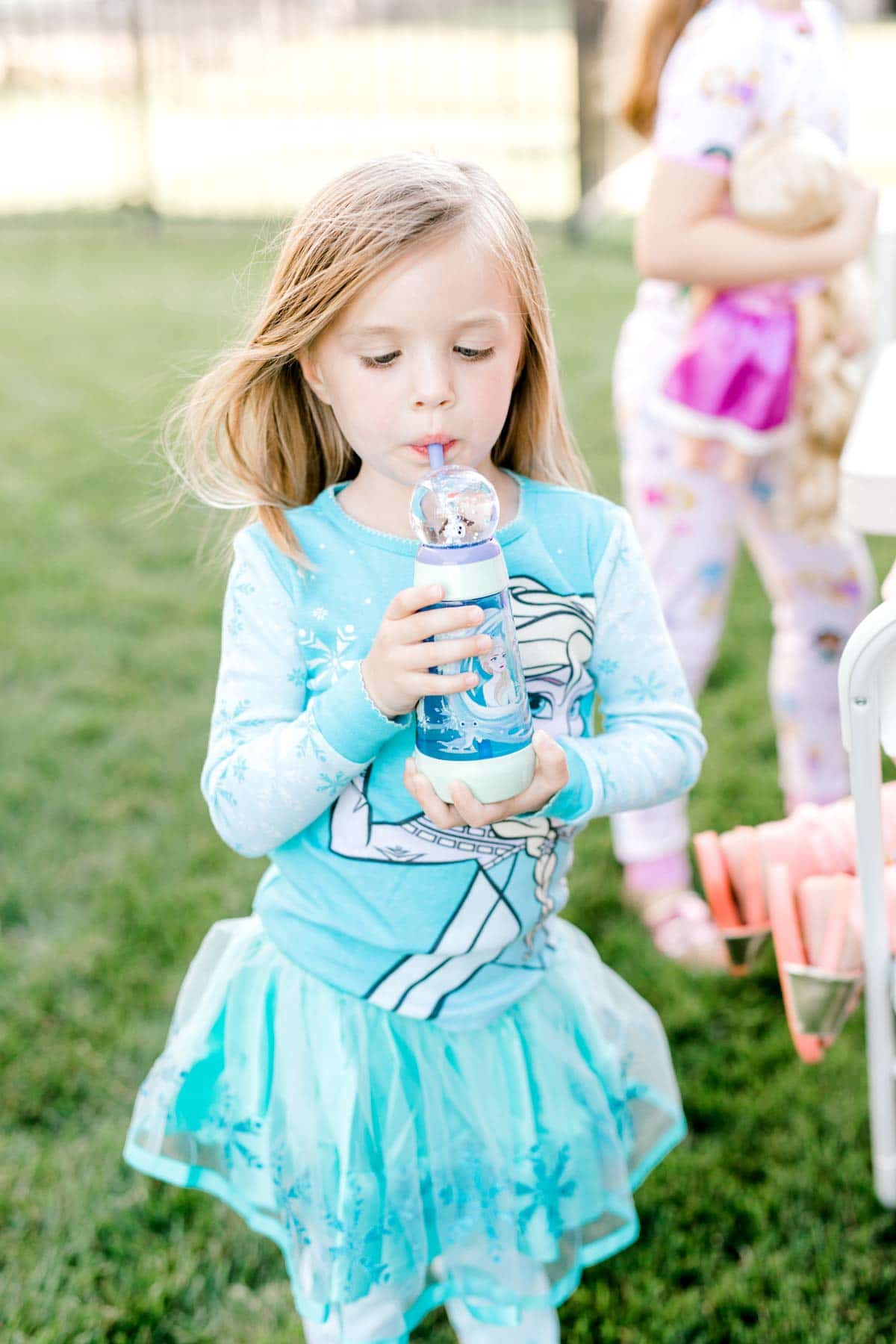 girl dressed in an elsa outfit with a water bottle