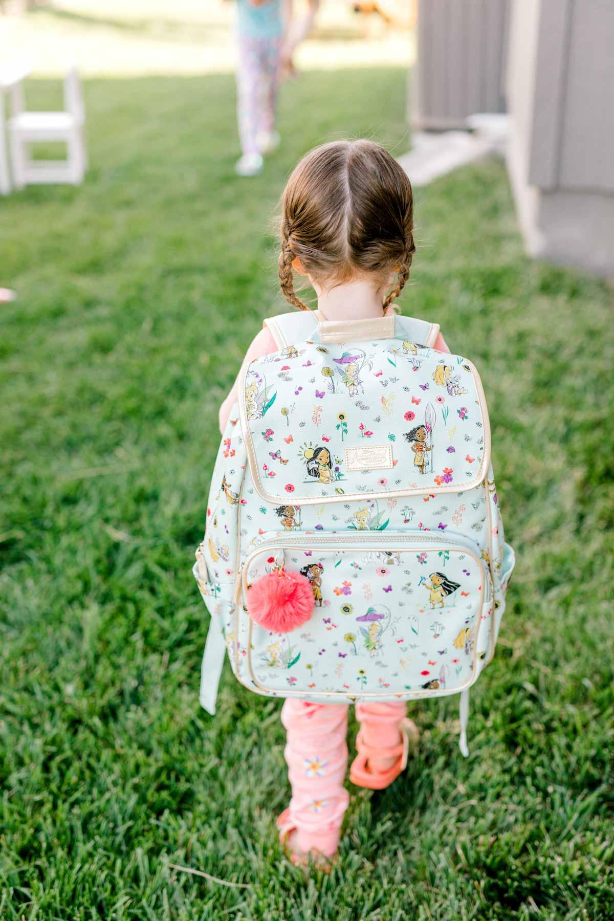 Girl wearing a Moana backpack