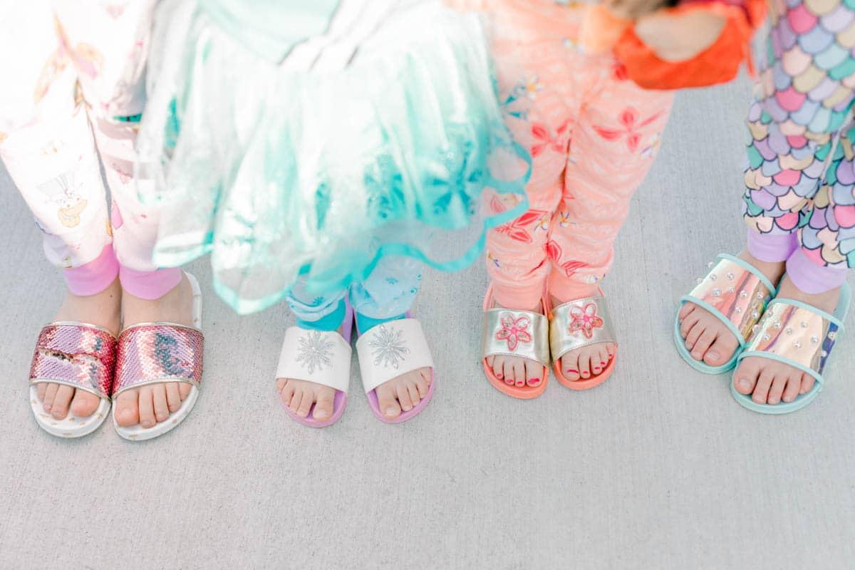 four girls wearing princess slippers