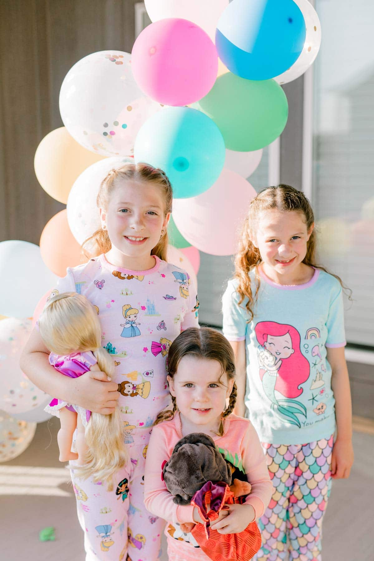 three girls standing in front of a balloon garland
