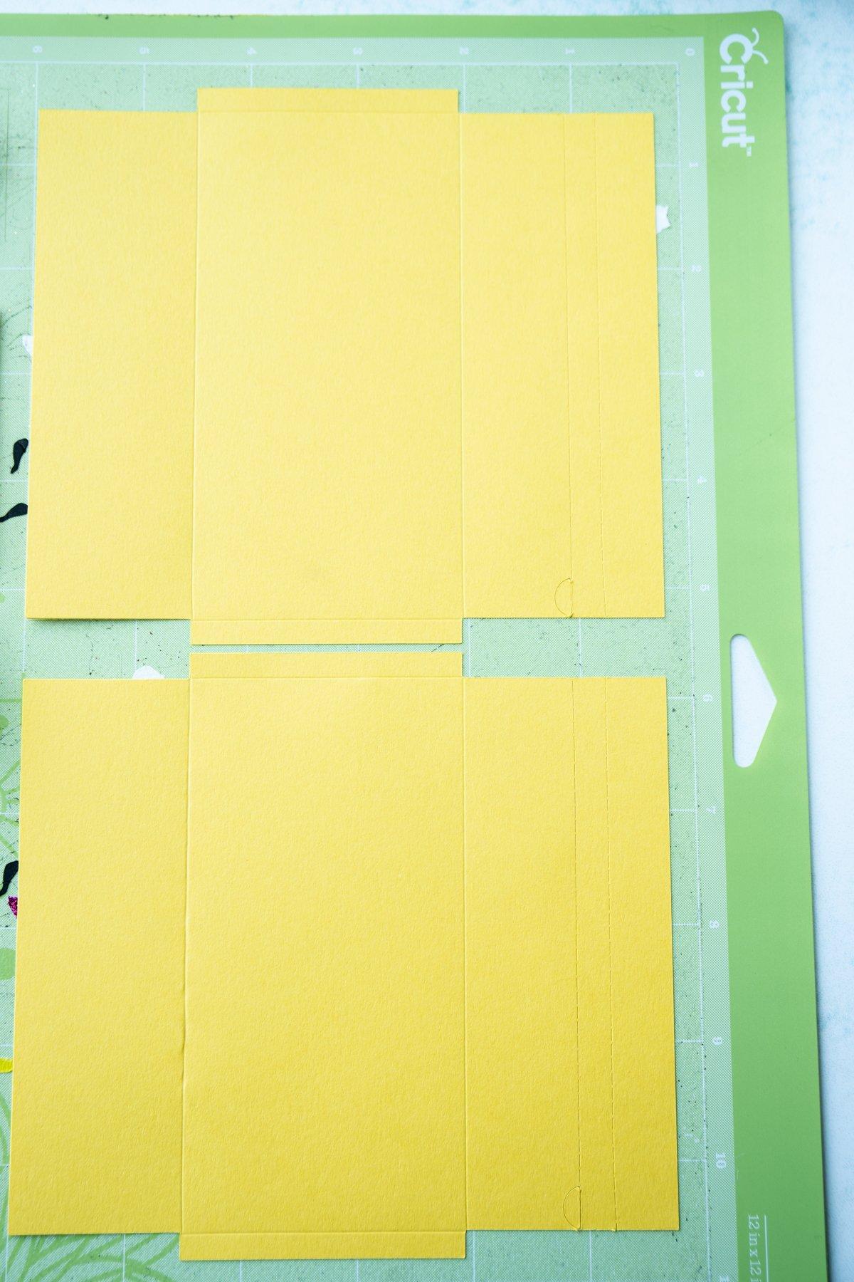 Flat yellow envelopes on a Cricut mat