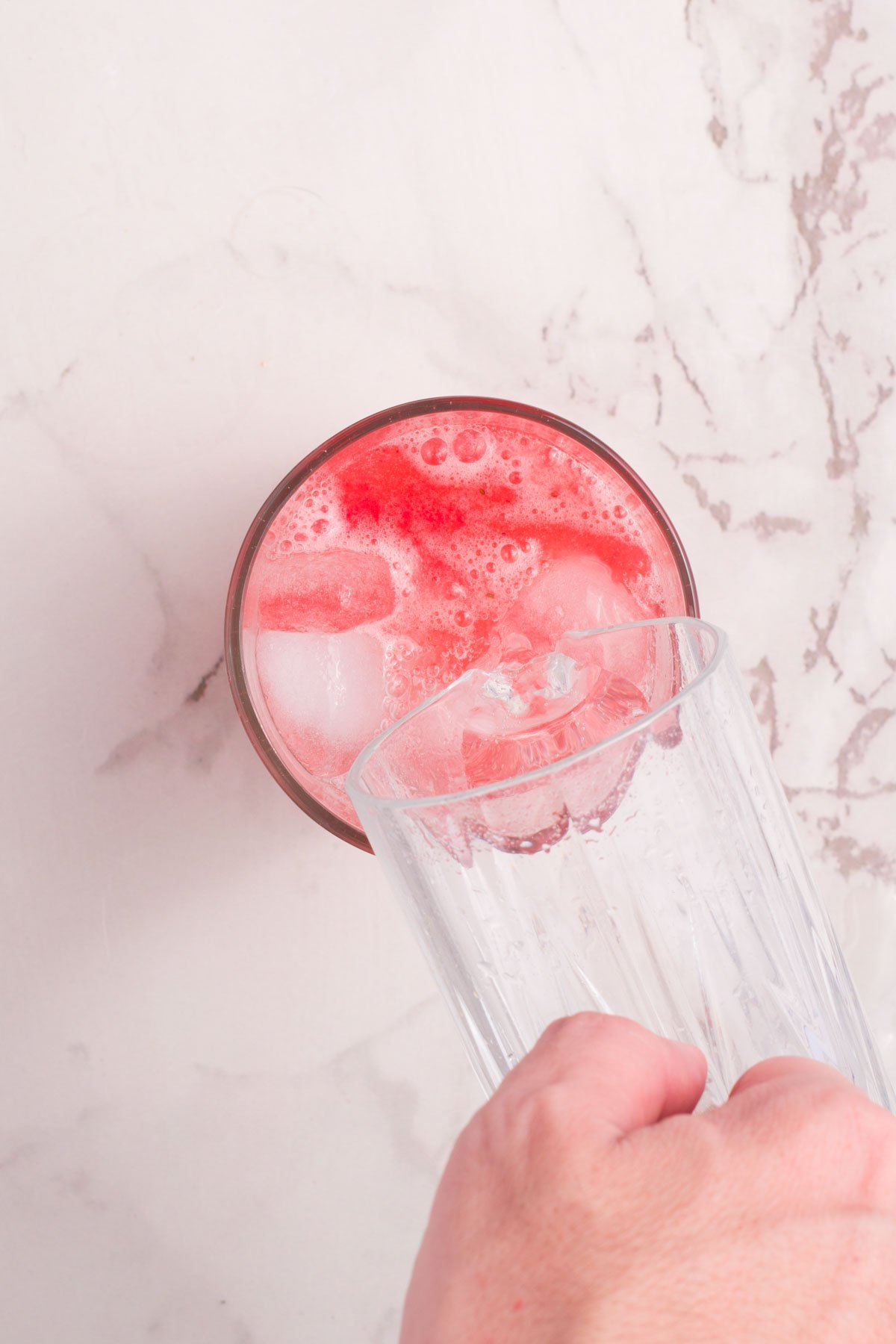 pouring ice into a glass of strawberry lemonade