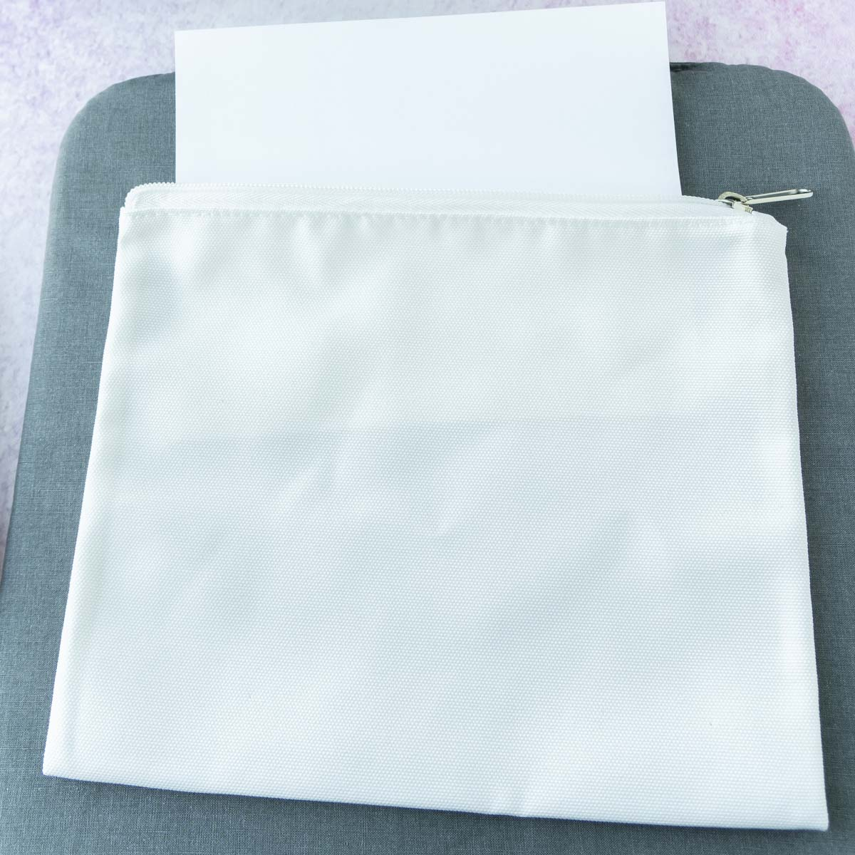 cardstock sticking out of a cosmetic bag blank