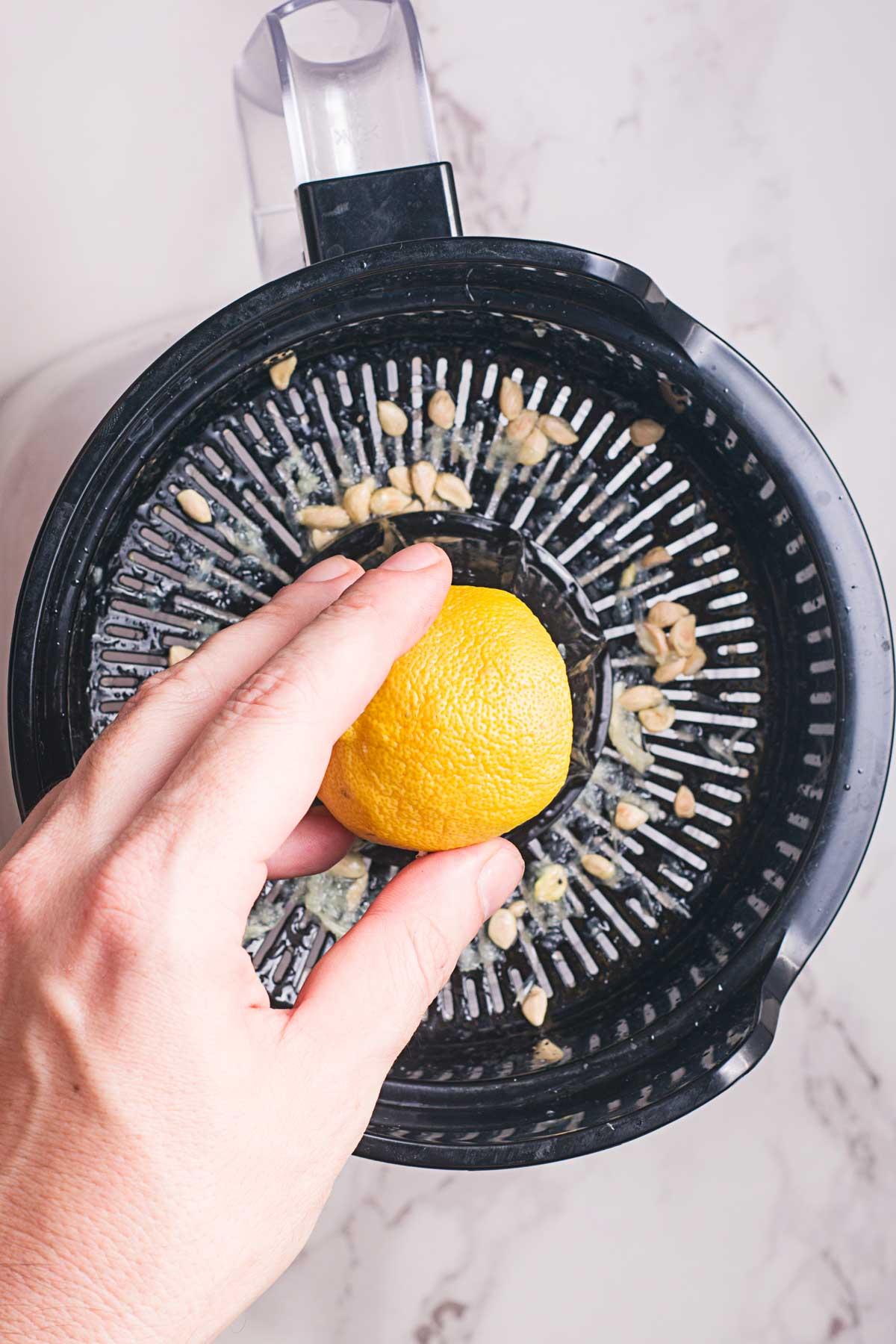 hand juicing a lemon on a juicer