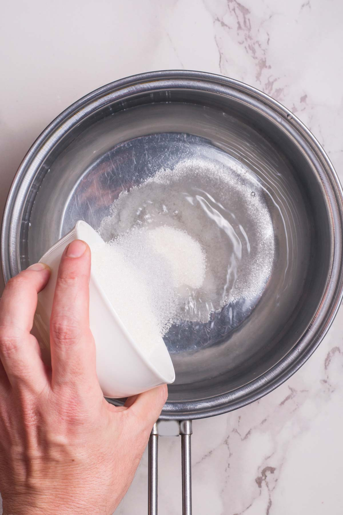 hand pouring sugar in a pan of water