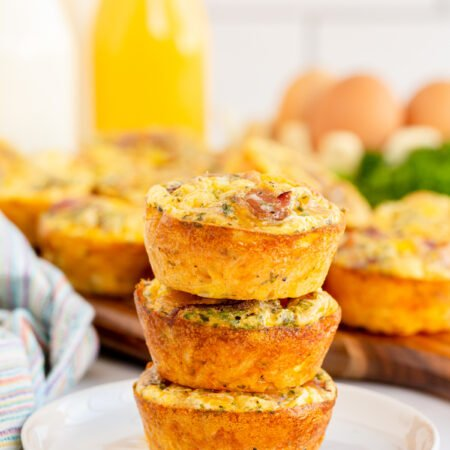 three stacked breakfast muffins on a white plate