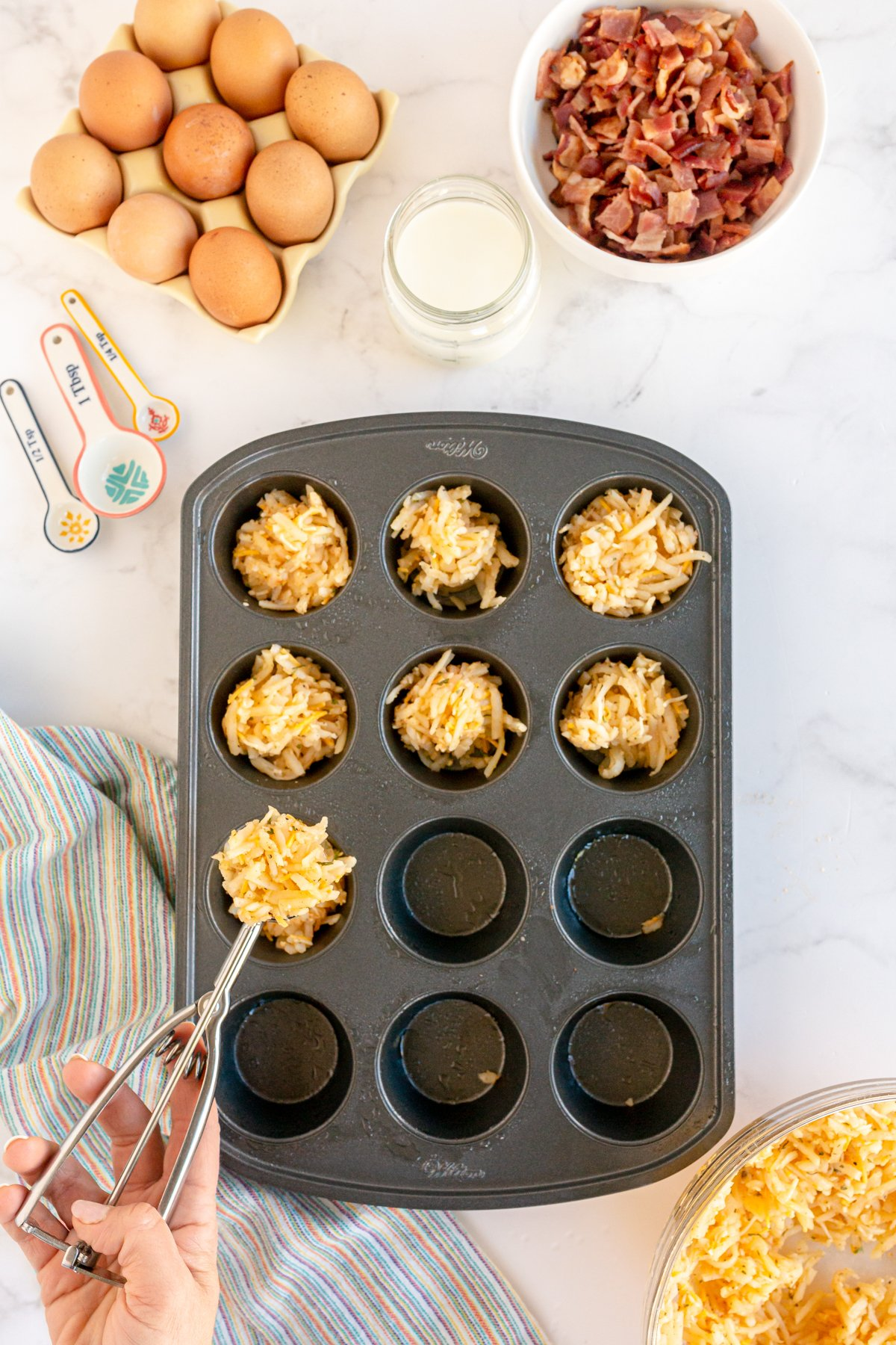 hand putting hash browns in muffin tins