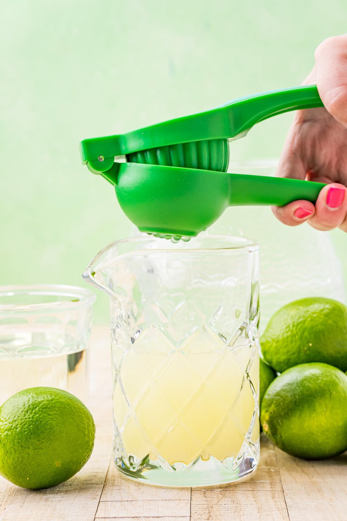 squeezing limes into a glass