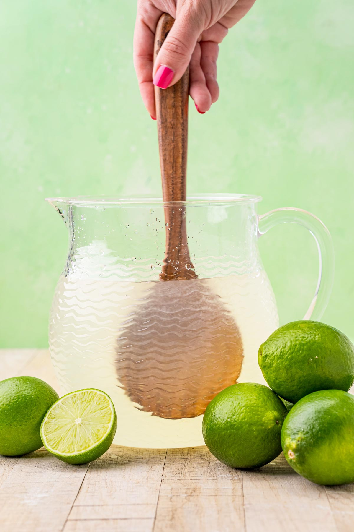stirring a glass pitcher of limeade