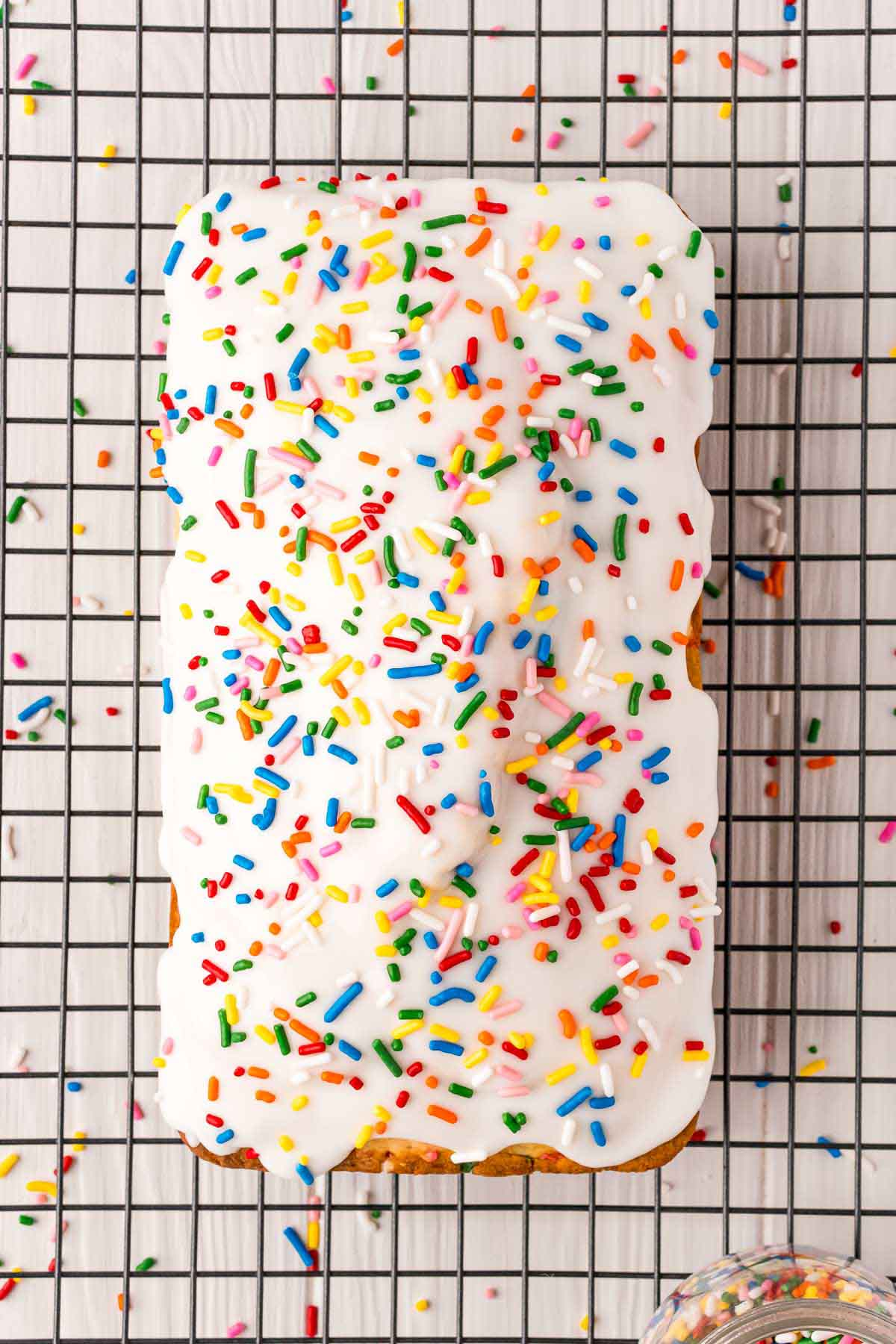 funfetti ice cream bread with icing on a wire rack