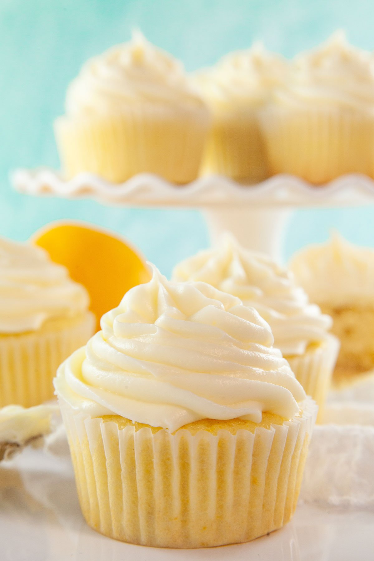 One lemon cupcake with a cake stand full behind it