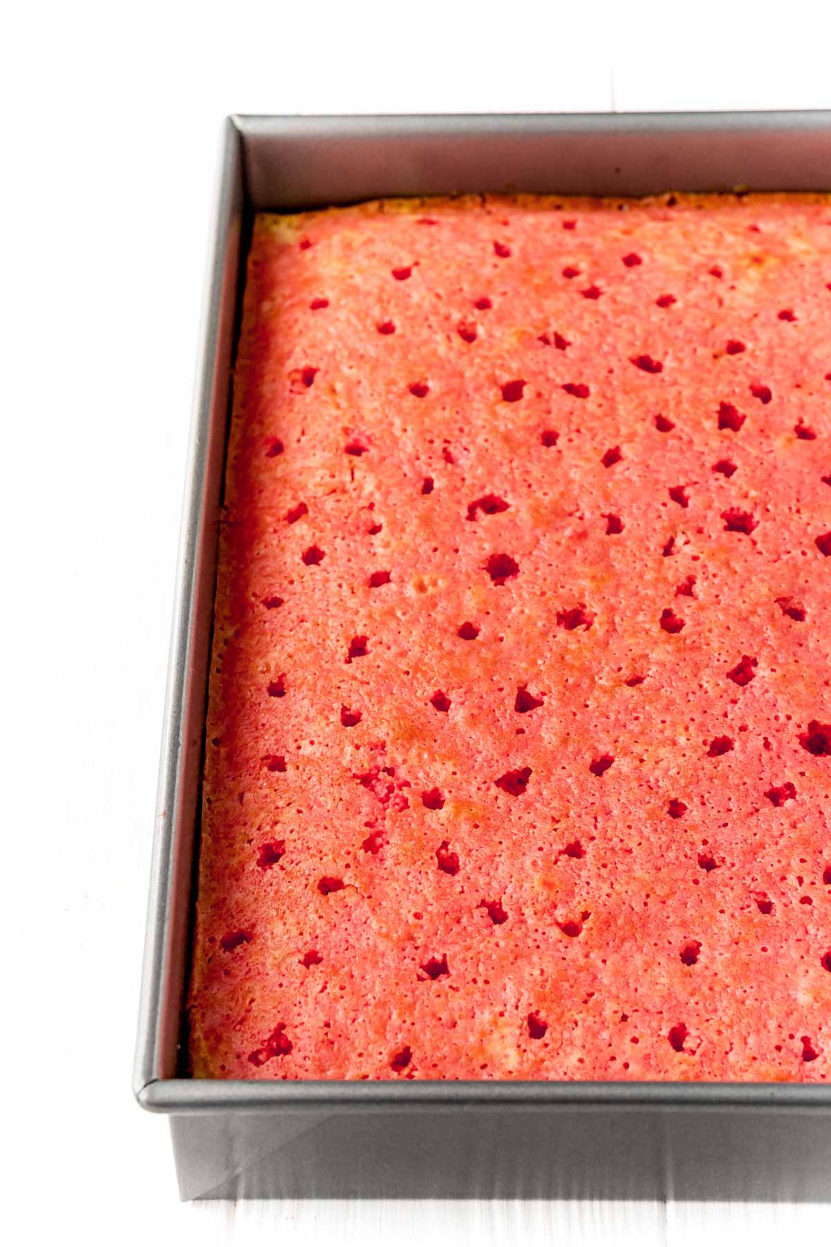 Raspberry jello poke cake chilling in a pan