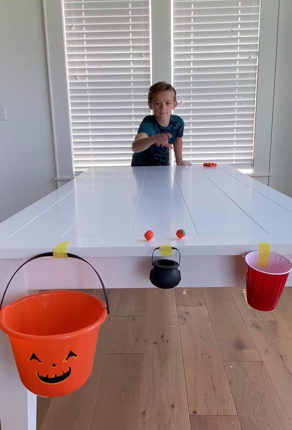 Kid sliding pumpkins across a table