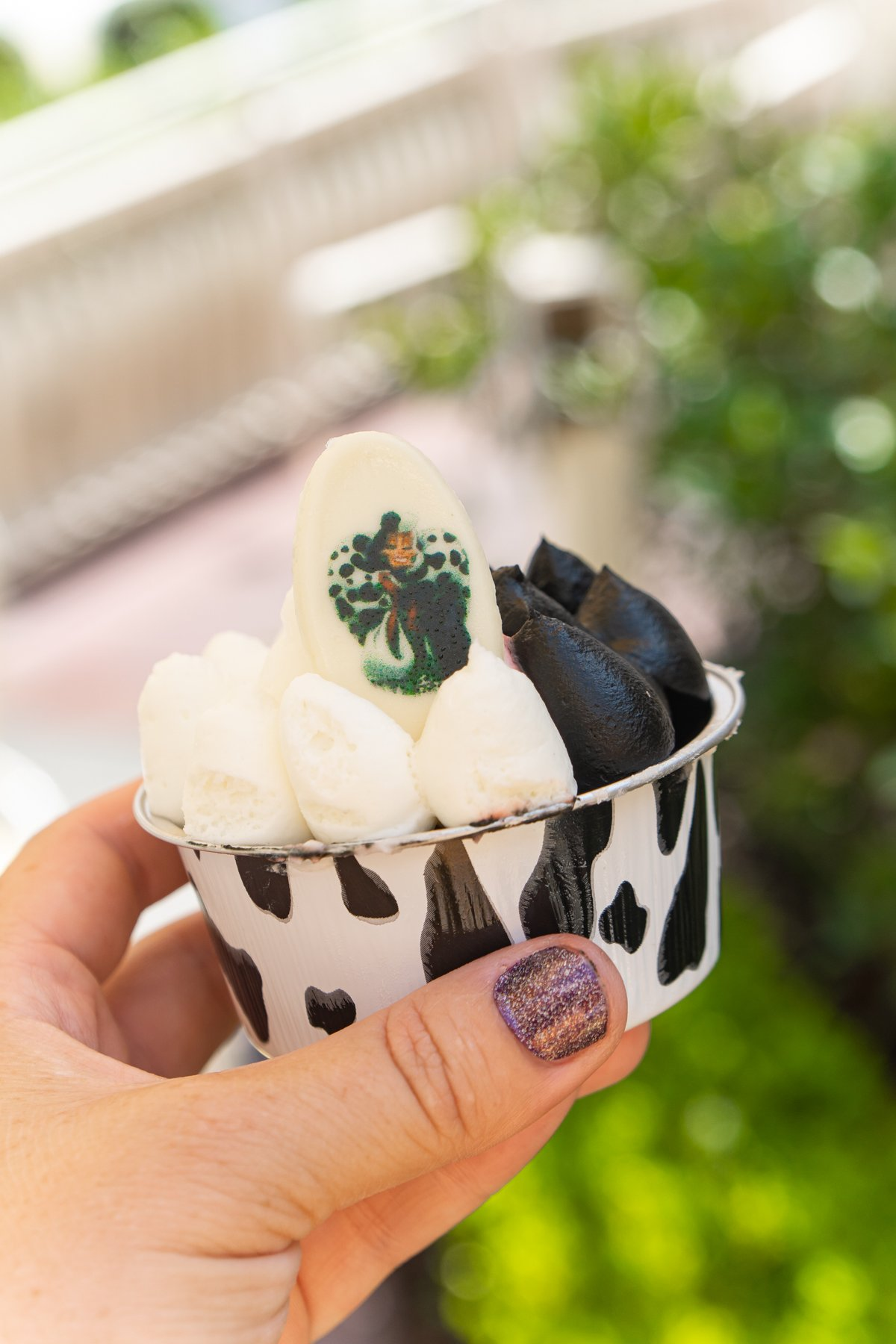 hand holding a cup with white and black frosting