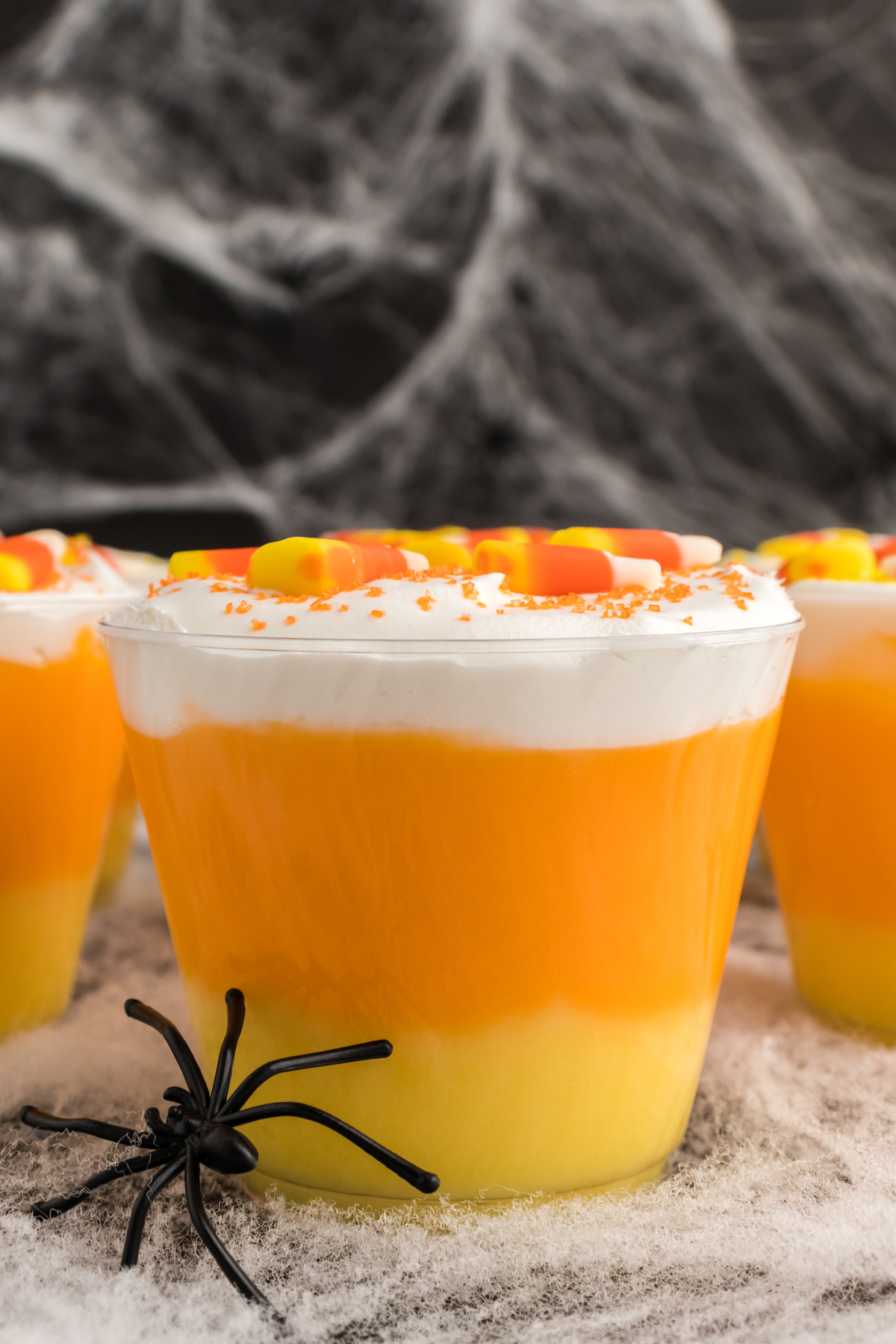 candy corn layered pudding dessert with a plastic spider