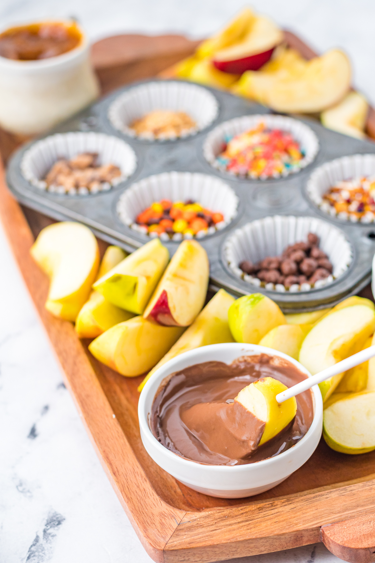 apple being dipped into melted chocolate