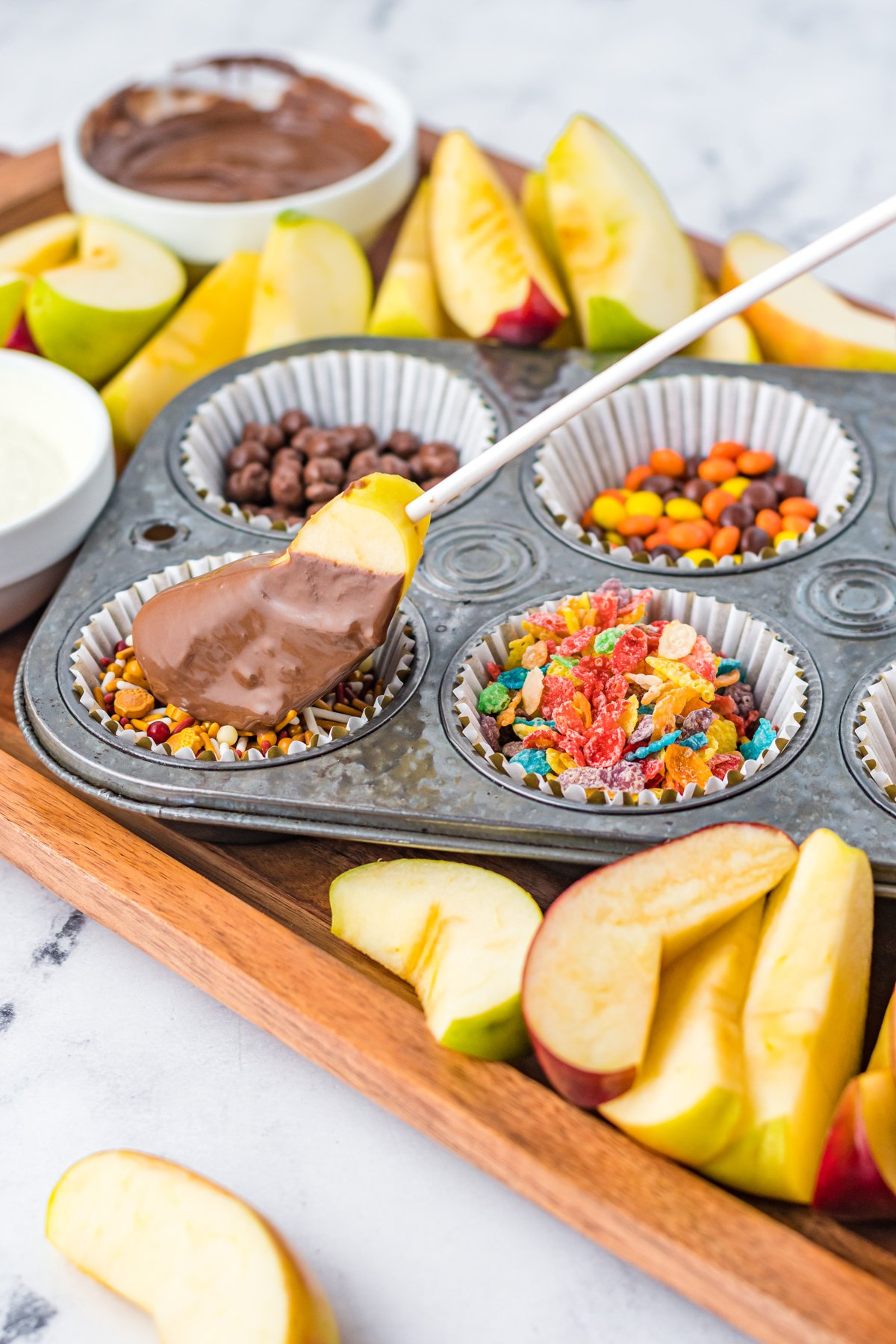 apple covered in chocolate being dipped in toppings