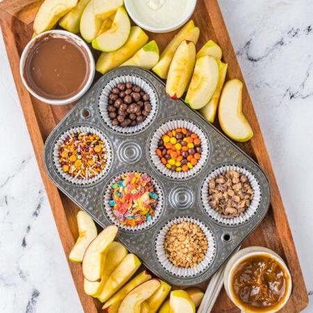 caramel apple bar toppings on a wood board