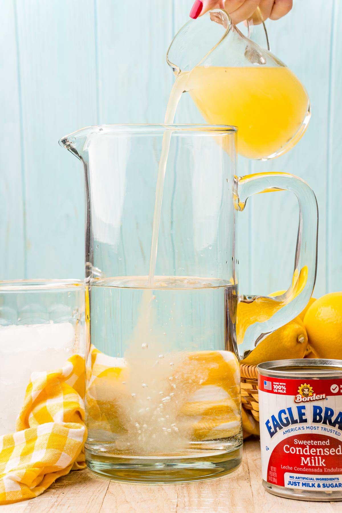 pouring lemon juice into a glass pitcher