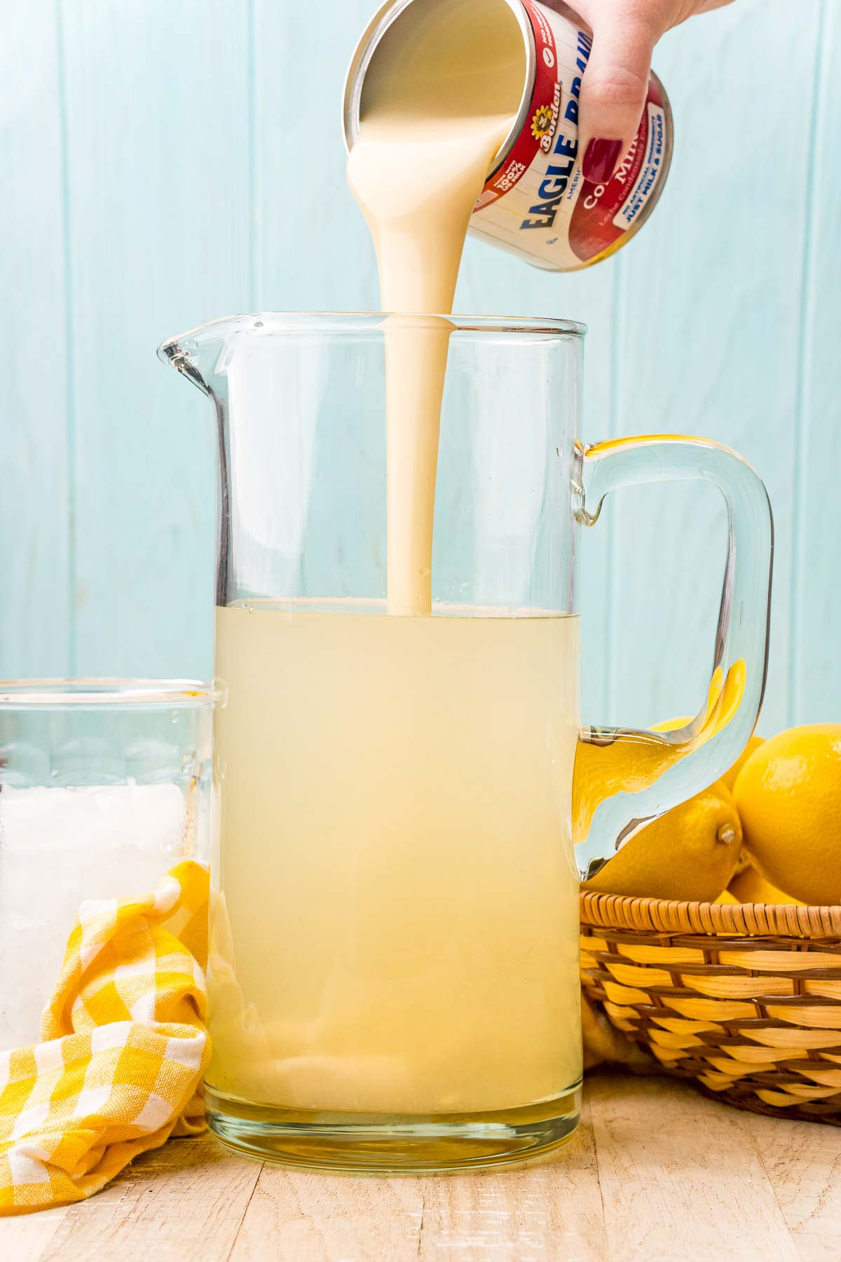 pouring sweetened condensed milk into a pitcher