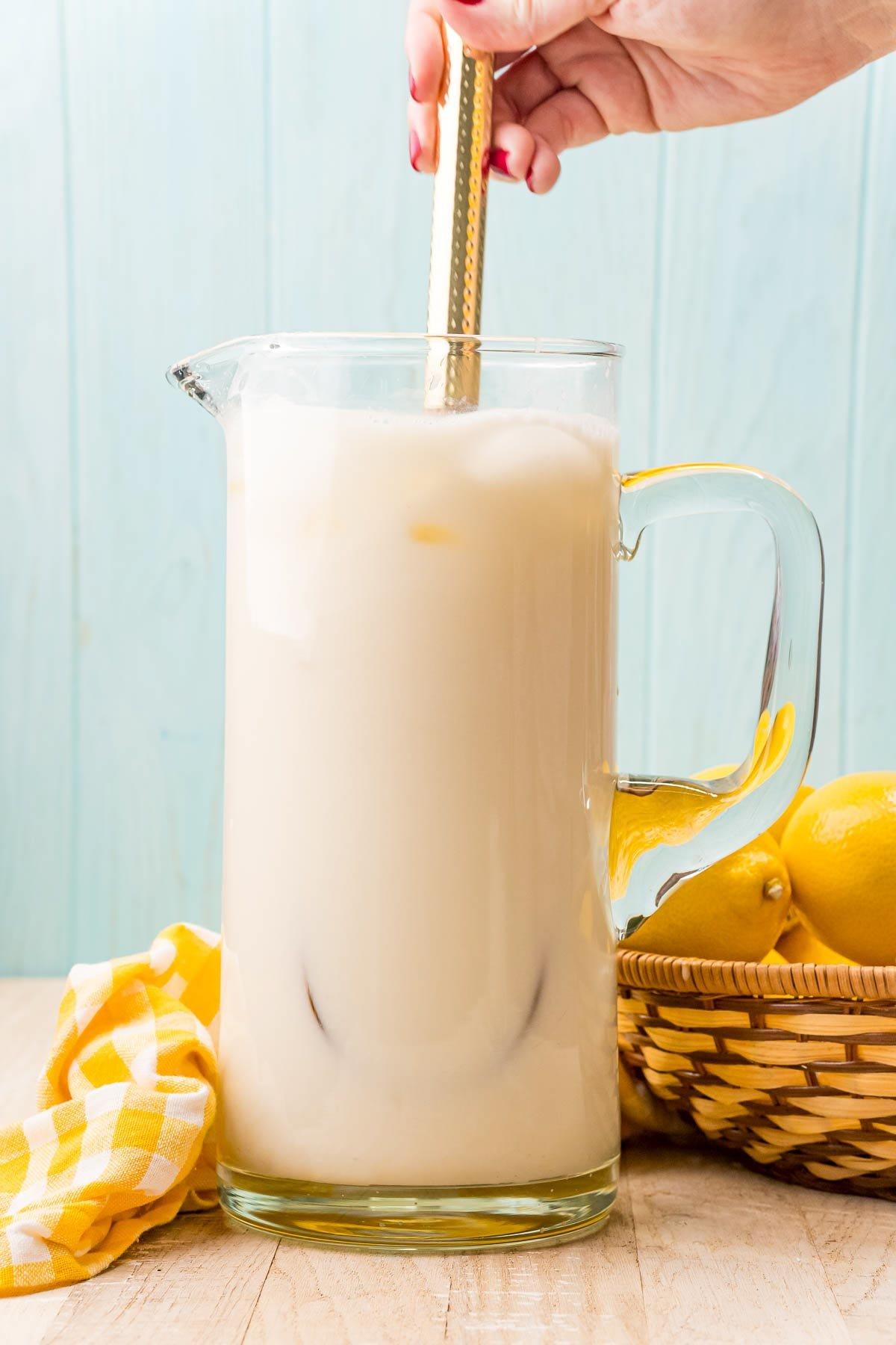 pitcher of creamy lemonade being stirred