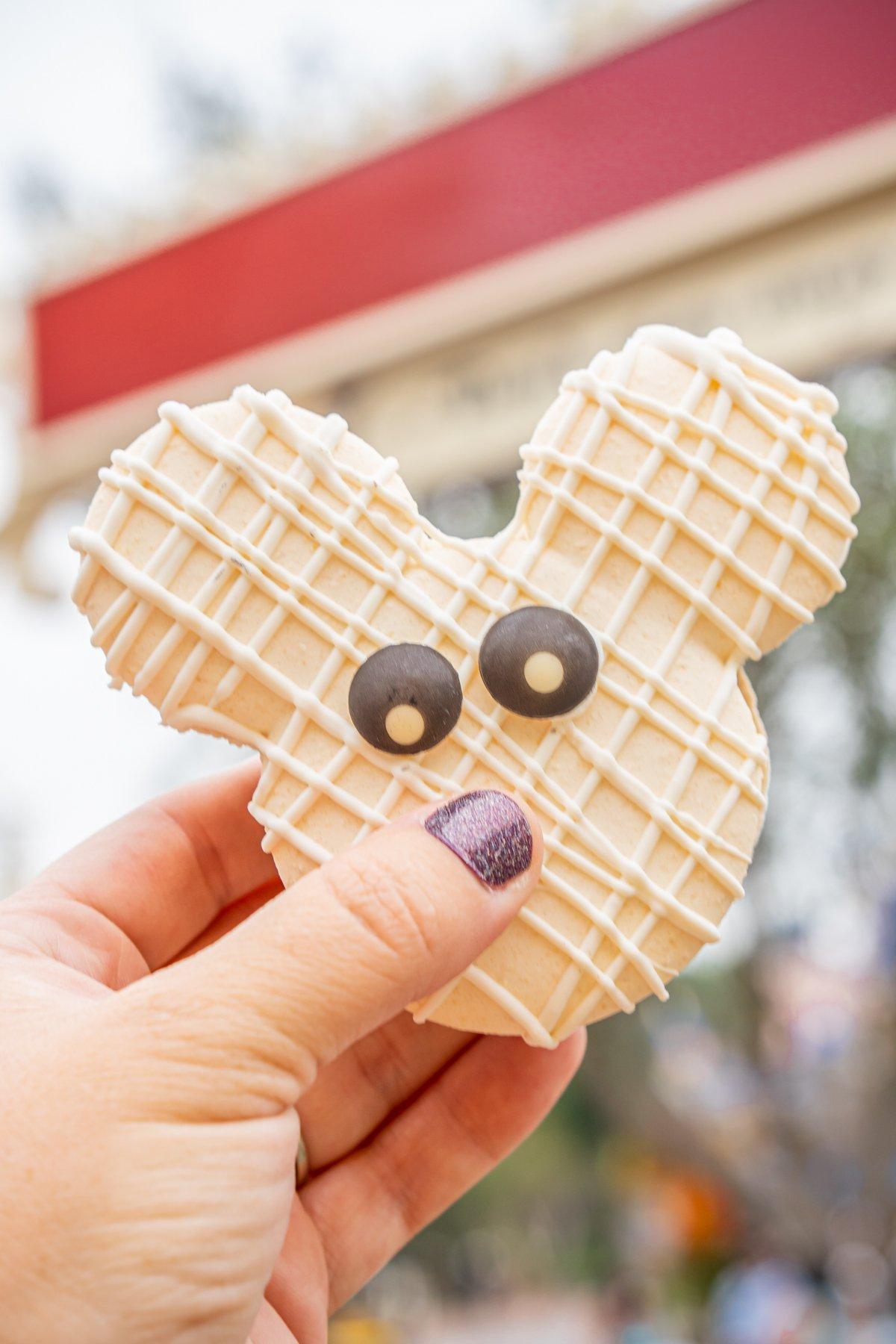 hand holding a white Mickey macaron