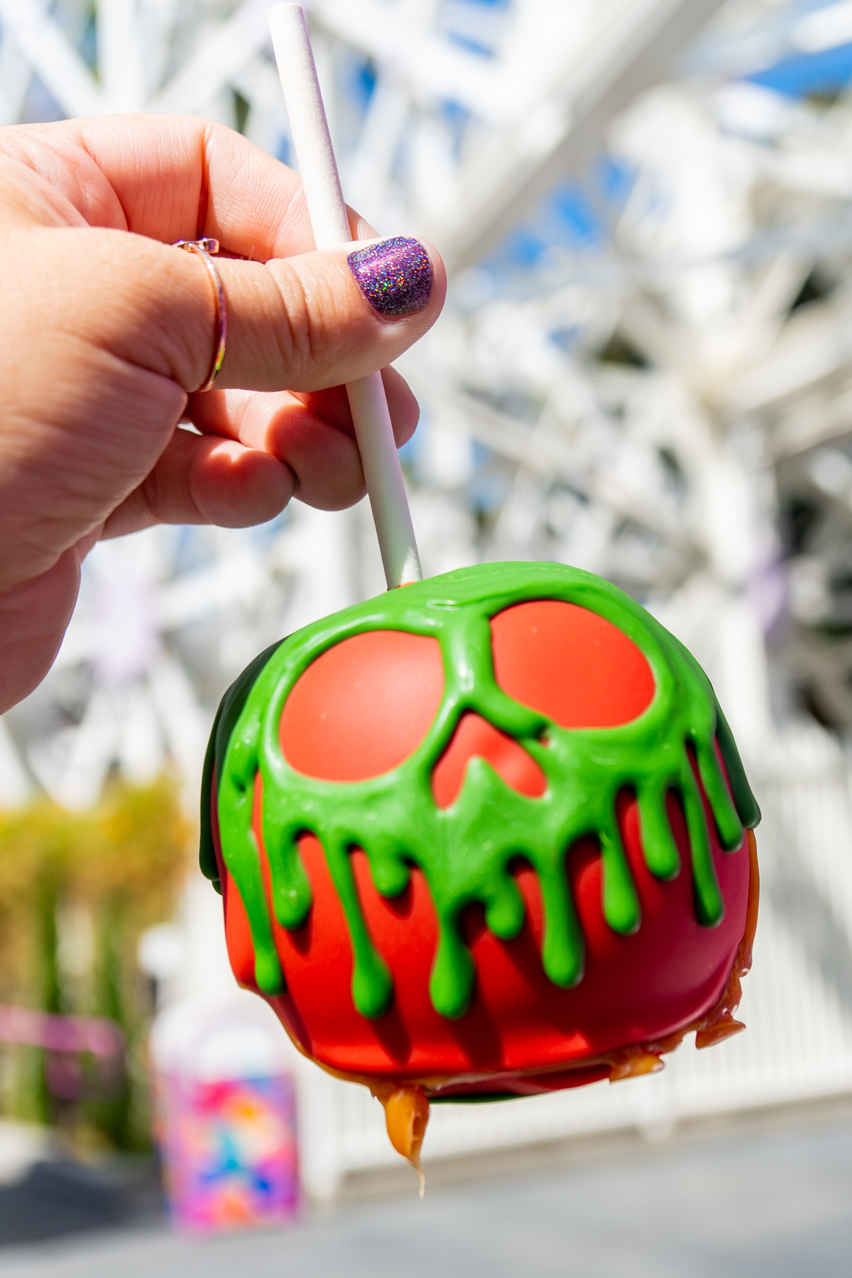 hand holding a poison apple caramel apple in front of Incredicoaster