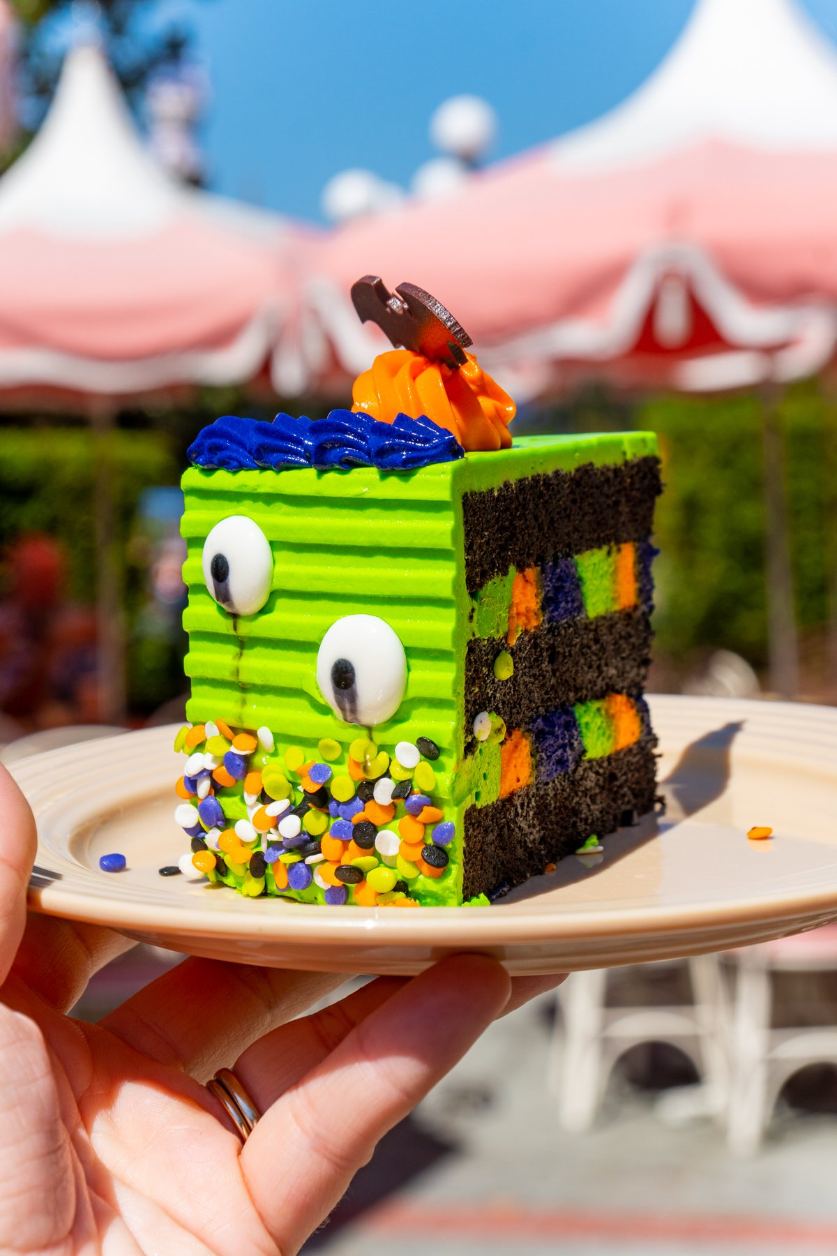 hand holding a plate with a Halloween layer cake