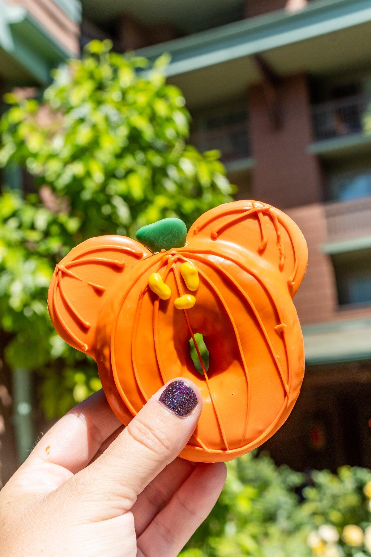 Mickey pumpkin donut in somoene's hand