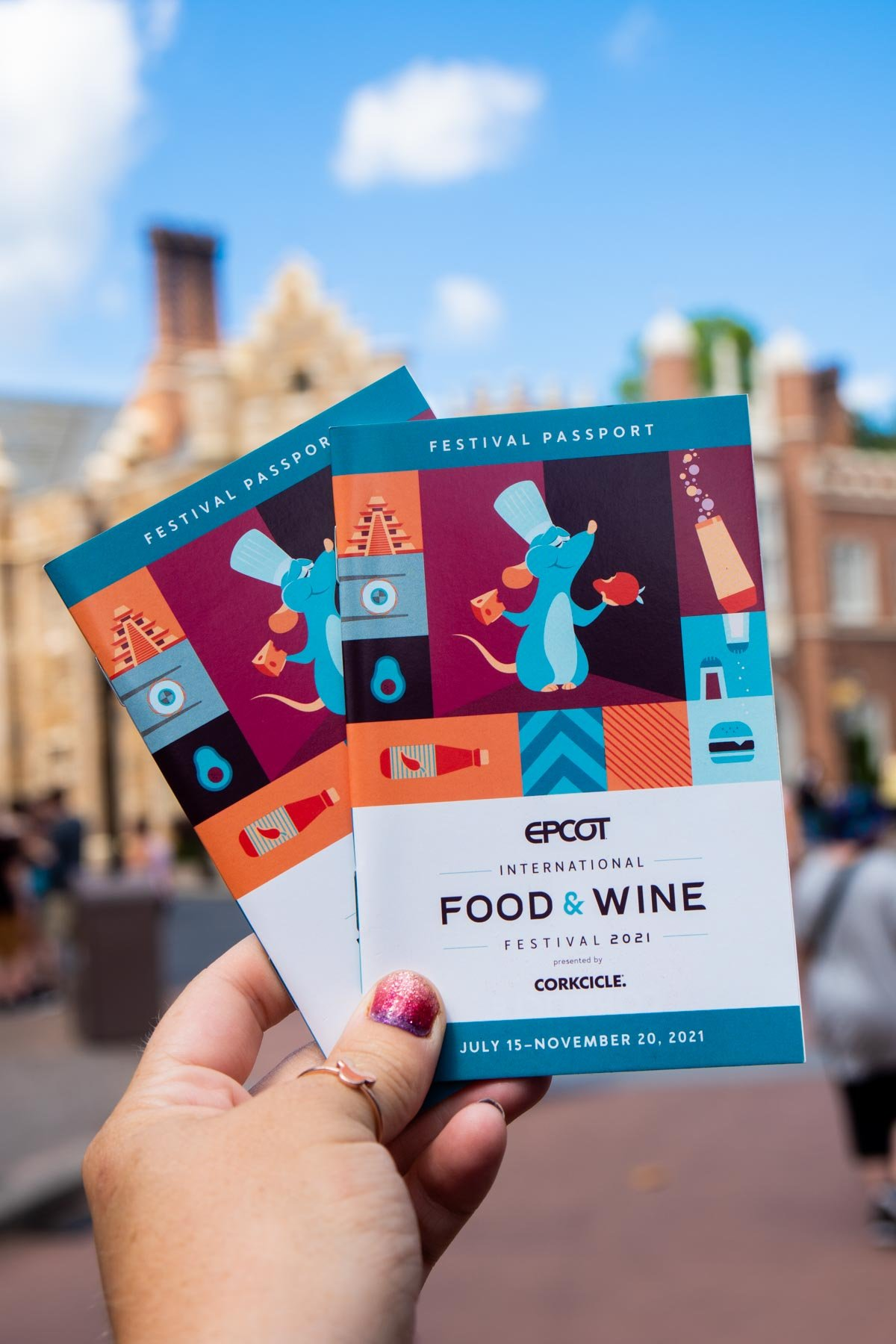 hand holding Epcot food and wine passports