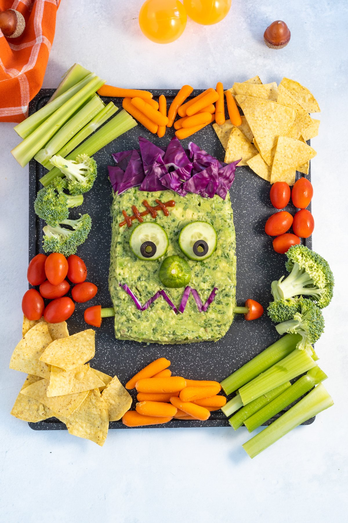 Frankenstein guacamole surrounded by chips, veggies, and more