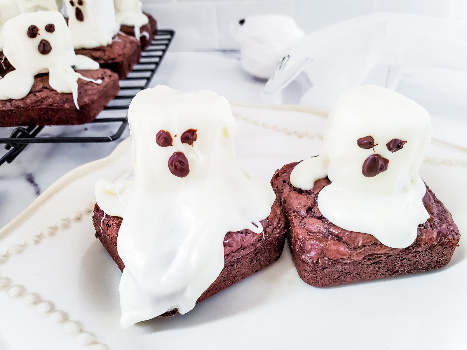 two cute ghost brownies on a white linen