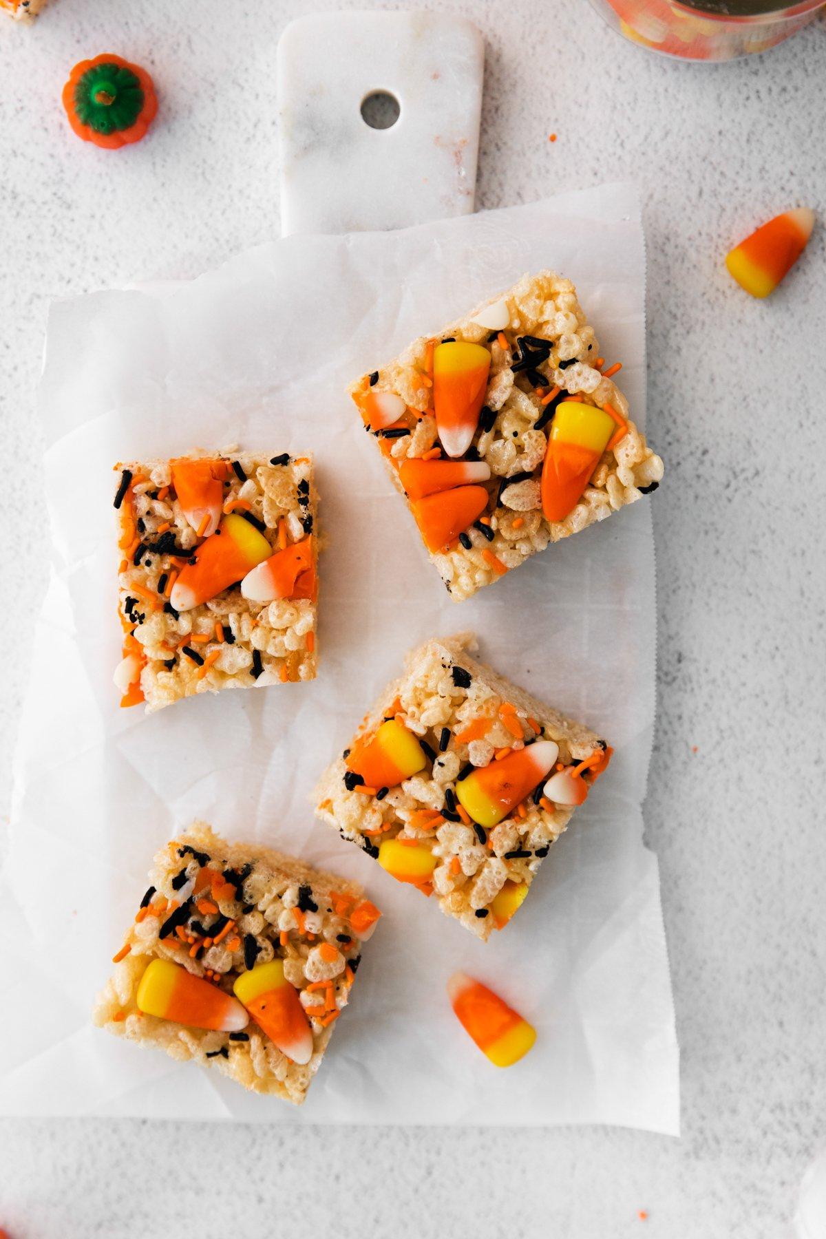 four Halloween rice krispie treats on a white cutting board