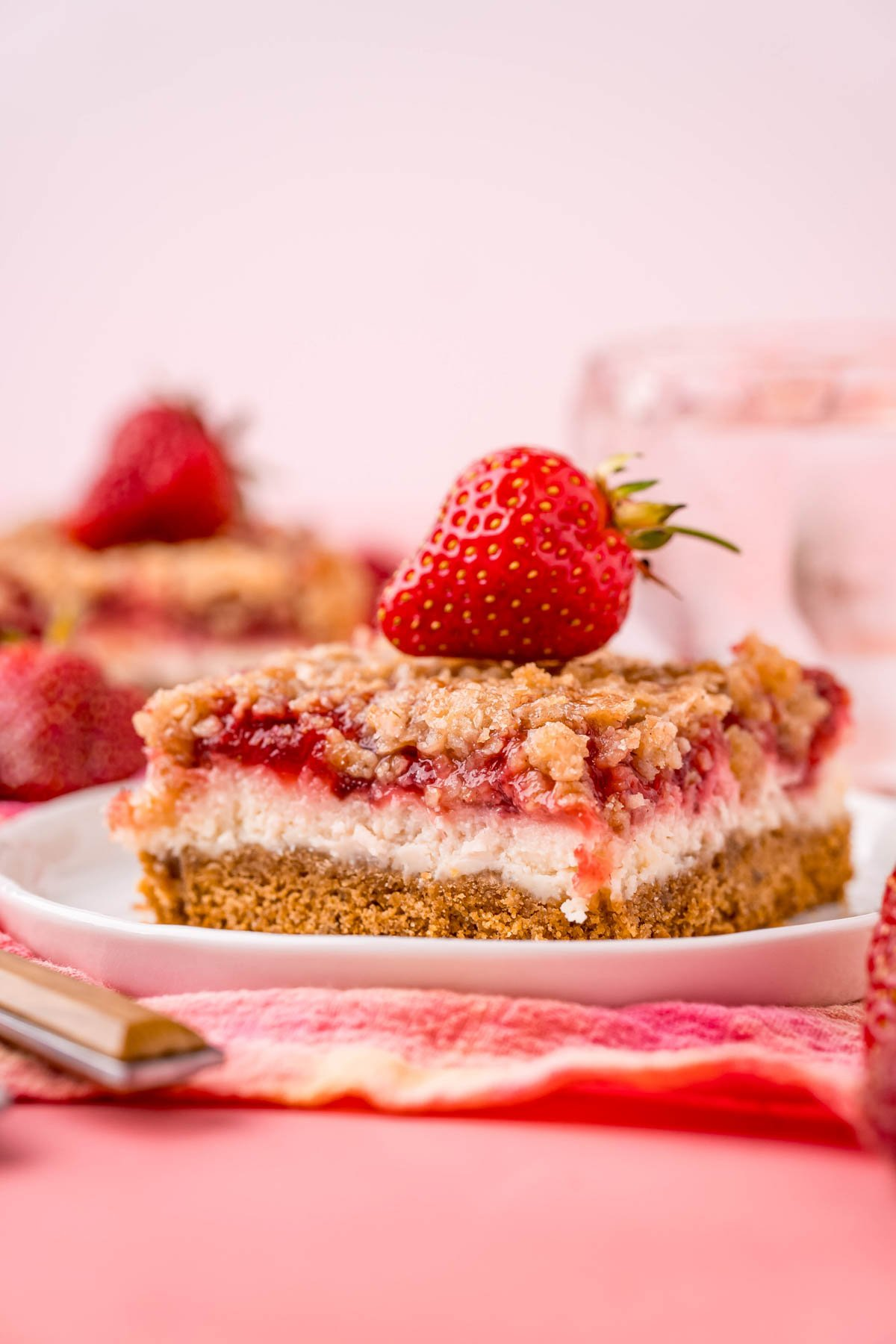 a white plate and two strawberry cheesecake bars