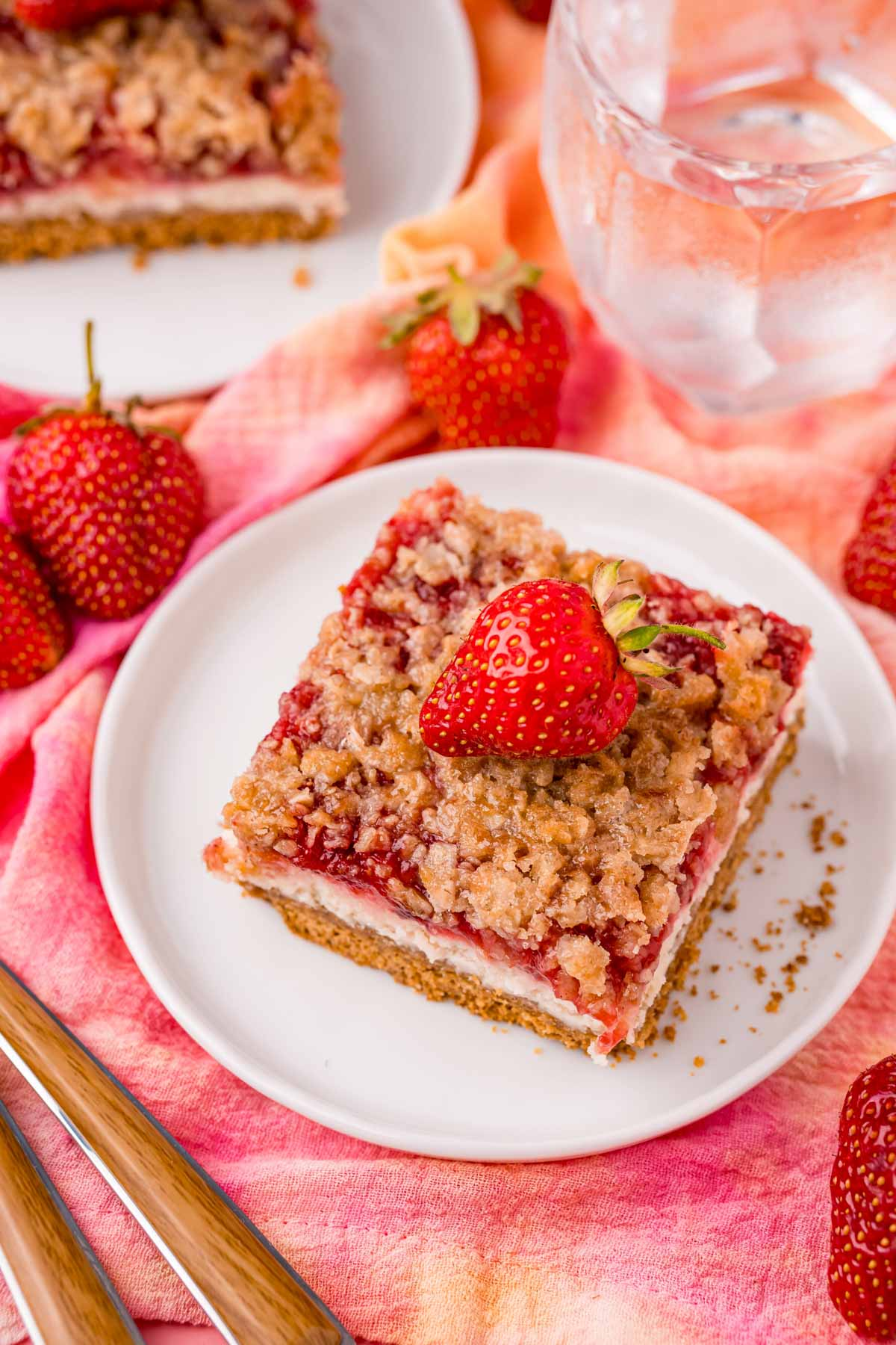 top down view of a strawberry cheesecake bar on a white plate