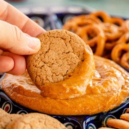 hand dipping a gingersnap in a pumpkin pie dip