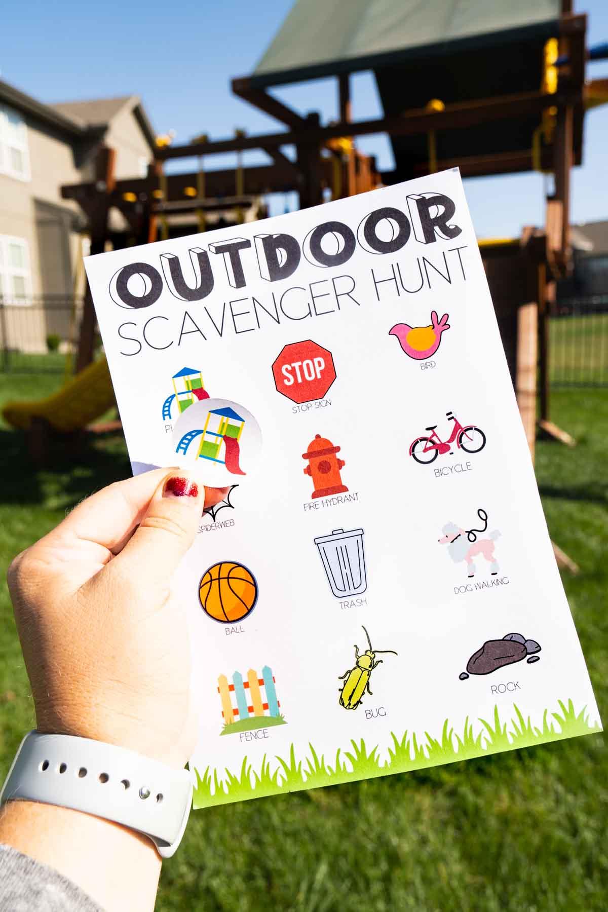 hand holding a playground sticker