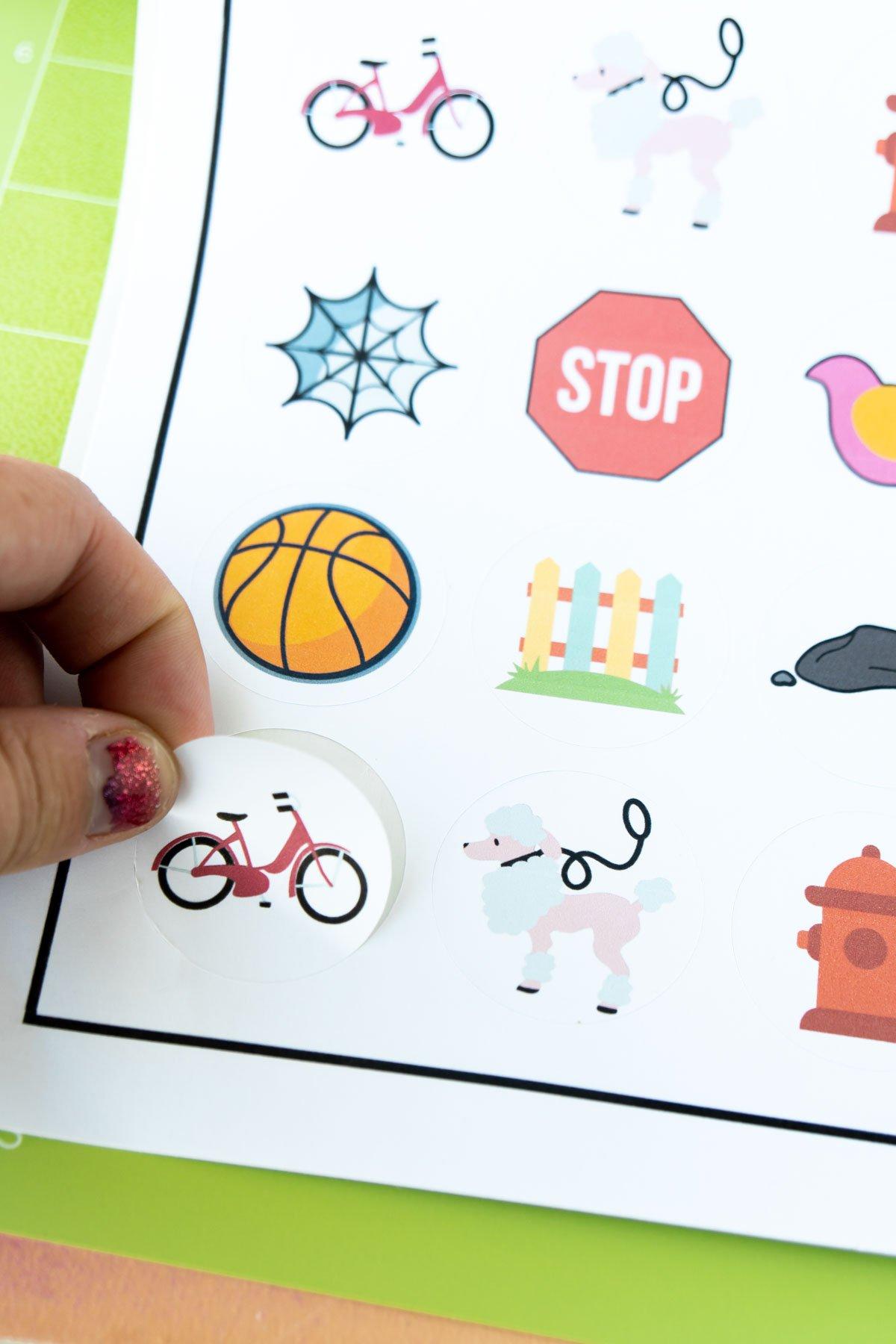 hand peeling a sticker off a sheet of stickers