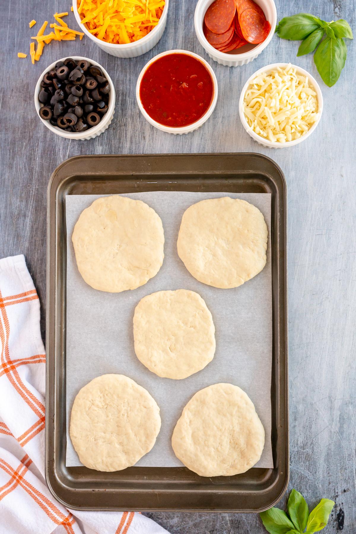 mini pizza dough circles on a baking sheet